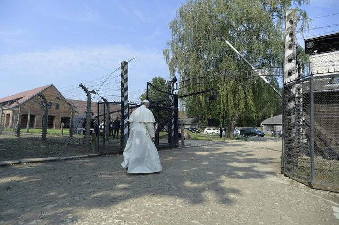 "Pope Francis walks through a gate with the words ""Arbeit macht frei"" at the former Nazi German concentration and extermination camp Auschwitz-Birkenau in Oswiecim"